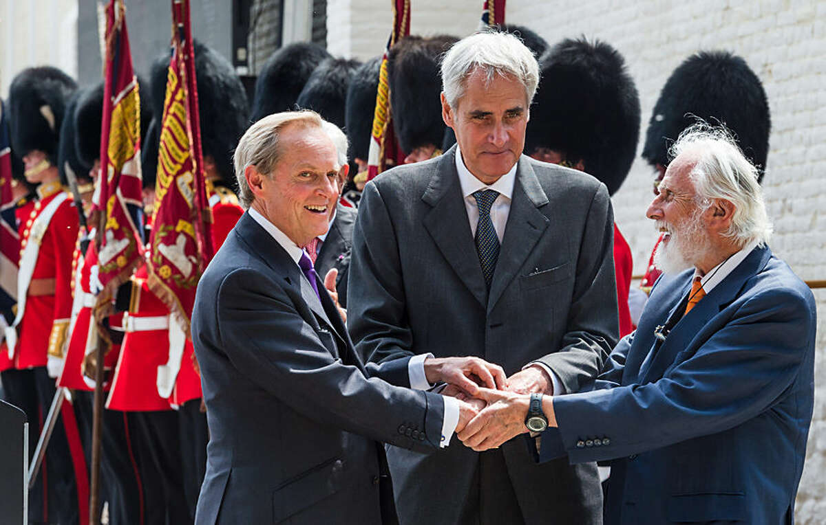 The Duke of Wellington, left, holds hands with Prince Charles Bonaparte, center, and Prince Bluecher von Wahlstatt during the ceremonial opening of the Hougoumont Farm in Braine-l'Alleud, near Waterloo, Belgium on Wednesday, June 17, 2015. Hougoumont Farm played a critical role in the outcome of the Battle of Waterloo, and the newly restored farm will open to the general public on June 18, 2015. (AP Photo/Geert Vanden Wijngaert, Pool)