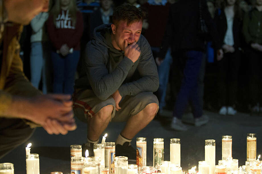 A mourner cries after placing a candle at a vigil for six Irish students Wednesday, June 17, 2015, in Berkeley, Calif. The six Irish students died when a balcony collapsed during a party. (AP Photo/Beck Diefenbach)