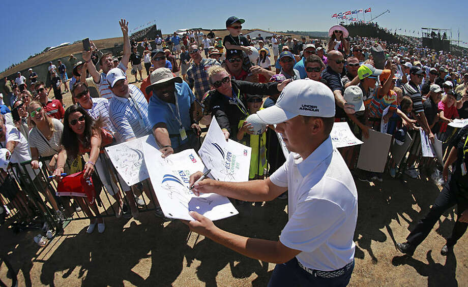 Jordan Spieth signs autographs after a practice round for the U.S. Open golf tournament at Chambers Bay on Wednesday, June 17, 2015 in University Place, Wash. (AP Photo/Charlie Riedel)