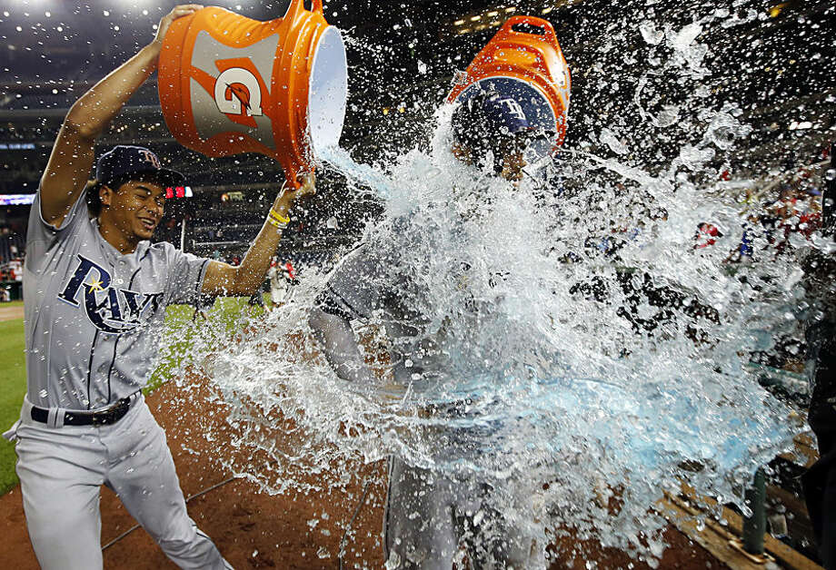 Tampa Bay Rays' David DeJesus, left, and Chris Archer, right, douse Steven Souza Jr. after a baseball game against the Washington Nationals at Nationals Park, Wednesday, June 17, 2015, in Washington. The Rays won 5-0. (AP Photo/Alex Brandon)