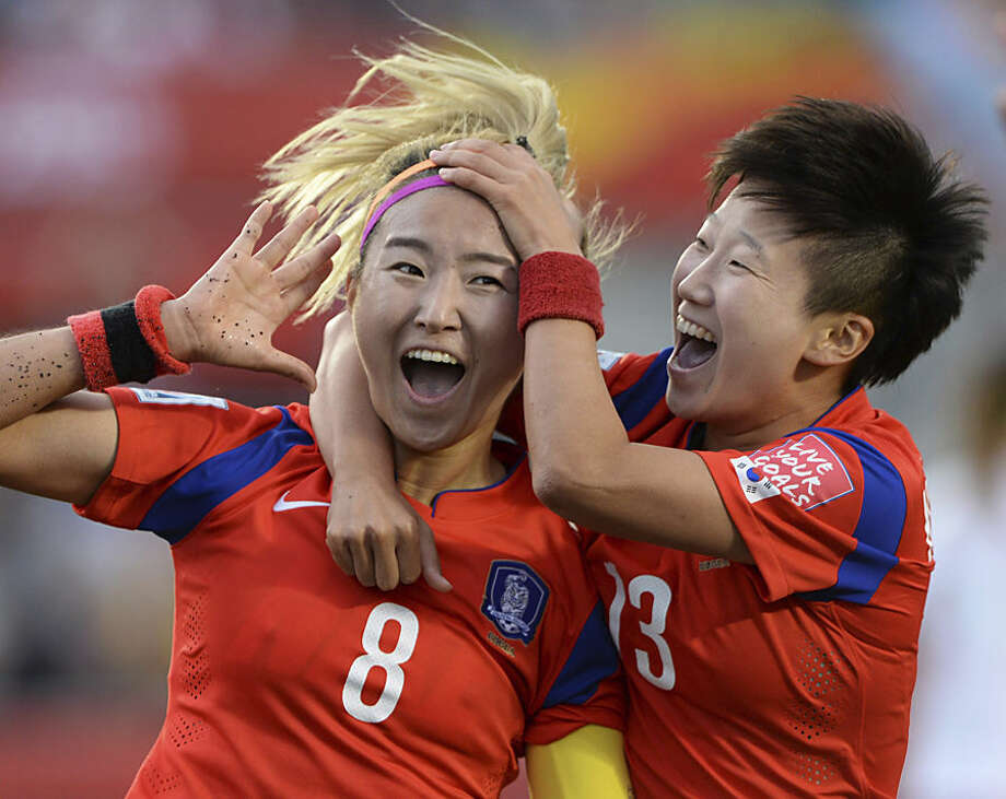 South Korea's Cho Sohyun (8) celebrates her goal with teammate Kwon Hahnul during the second half of a FIFA Women's World Cup soccer match, Wednesday, June 17, 2015 in Ottawa, Ontario, Canada, (Sean Kilpatrick/The Canadian Press via AP) MANDATORY CREDIT