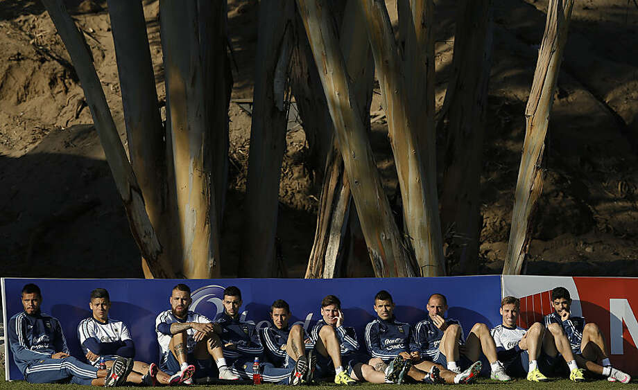 Players of Argentina's national soccer team, from left, Sergio Romero, Marcos Rojo, Nicolas Otamendi, Javier Pastore, Angel Di Maria, Lionel Messi, Sergio Aguero, Pablo Zabaleta, Lucas Biglia and Ezequiel Garay sit on the field as they watch a training session of substitutes players in La Serena, Chile, Wednesday, June 17, 2015. Argentina will face Jamaica in a Copa America soccer match on Saturday. (AP Photo/Andre Penner)