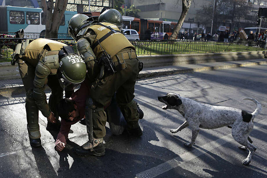 Police detain a protester as a dog barks at them during a teachers' demonstration in Santiago, Chile, Wednesday, June 17, 2015. A teachers union is in its second week on strike as they demand increased salaries and participation in educational reform. (AP Photo/Jorge Saenz)