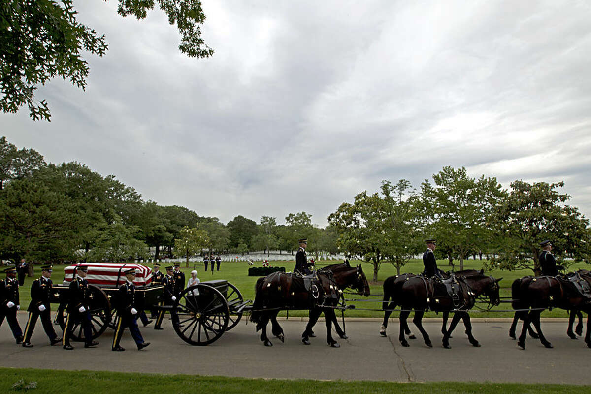 An army caisson team carries a casket containing the remains of four soldiers missing from Vietnam War: Army Chief Warrant Officer 3 James L. Phipps, Army Chief Warrant Officer 3 Rainer S. Ramos, Army Staff Sgt. Warren Newton, Army Spc. Fred J. Secrist, during a group burial services, Wednesday, June 17, 2015, at Arlington National Cemetery in Arlington, Va. (AP Photo/Jose Luis Magana)