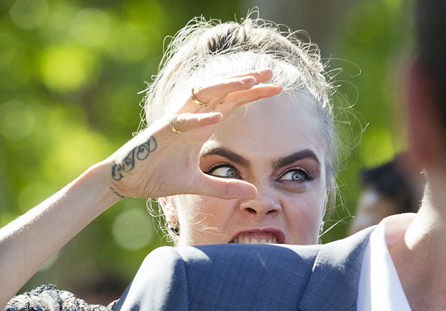 British Model Cara Delevingne gestures, during a photocall for the movie, 'Paper Towns' or 'La Face Cachee de Margo', in front of the Eiffel Tower, in Paris, France, Wednesday, June 17, 2015. (AP Photo/Jacques Brinon)