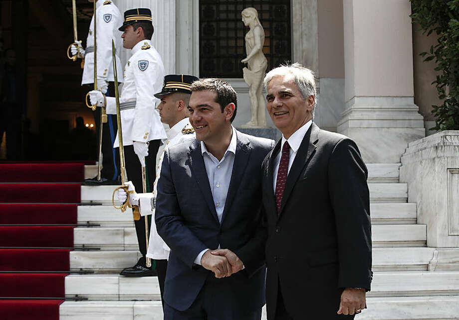Greece's Prime Minister Alexis Tsipras, left, welcomes visiting Austrian Chancellor Werner Faymann in Athens, Greece, on Wednesday, June 17, 2015. Faymann pays a one-day visit to Athens. (AP Photo/Yorgos Karahalis)