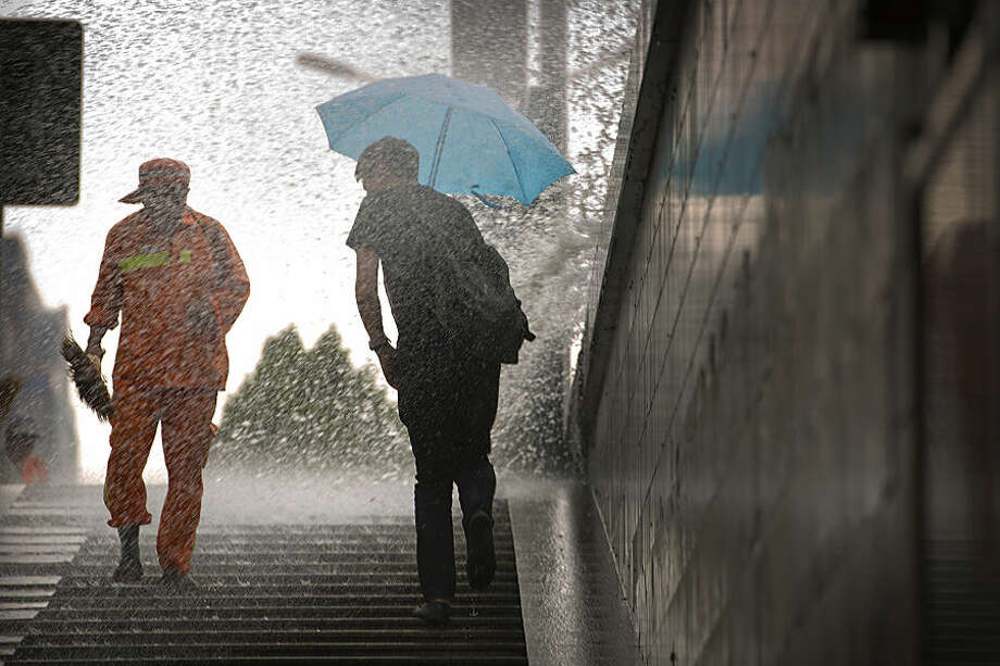A maintenance worker and a pedestrian are splashed by spray from a passing bus during a rainstorm in Beijing Wednesday, June 17, 2015. Although Beijing is in a semi-dry climate, it receives much of its annual precipitation during the summer months. (AP Photo/Mark Schiefelbein)