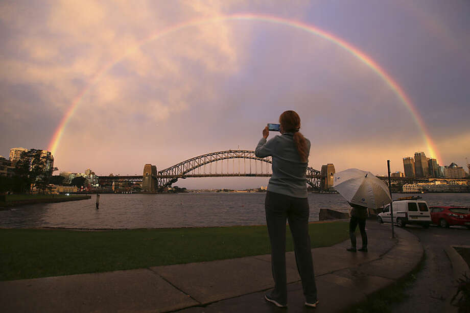 A woman takes a photograph as a rainbow forms over the Harbour Bridge on a wet day in Sydney Wednesday, June 17, 2015. (AP Photo/Rick Rycroft)