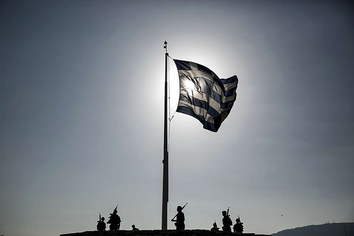 An army contingent stands below a fluttering Greek flag after a hoisting ceremony at the Acropolis hill in Athens, Greece Thursday, June 18, 2015. Greece and its creditors publicly blamed one another for an impasse in bailout talks, on the eve of a eurozone finance ministers' meeting billed as key to their outcome. (AP Photo/Yorgos Karahalis)