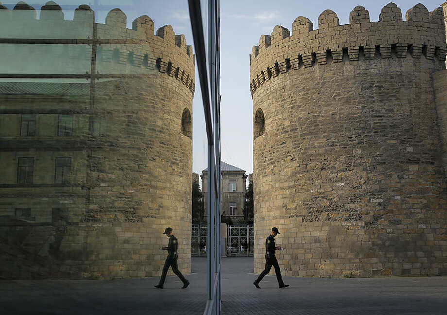 A police officer walks past a fortress tower reflected in the glass pane of a modern building in the old city of Baku, Azerbaijan, Wednesday, June 17, 2015. The 2015 European Games are held in Baku till June 28. (AP Photo/Dmitry Lovetsky)
