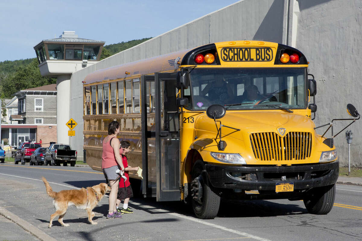 A woman accompanies her young son as he is picked up by a school bus next to the Clinton Correctional Facility, Wednesday, June 17, 2015 in Dannemora, N.Y. Search teams are back in the woods of northern New York looking for two convicted murderers who broke out of the maximum-security prison a week and a half ago. More than 800 law enforcement officers are in the 12th day of searching for David Sweat and Richard Matt. (AP Photo/Mark Lennihan)