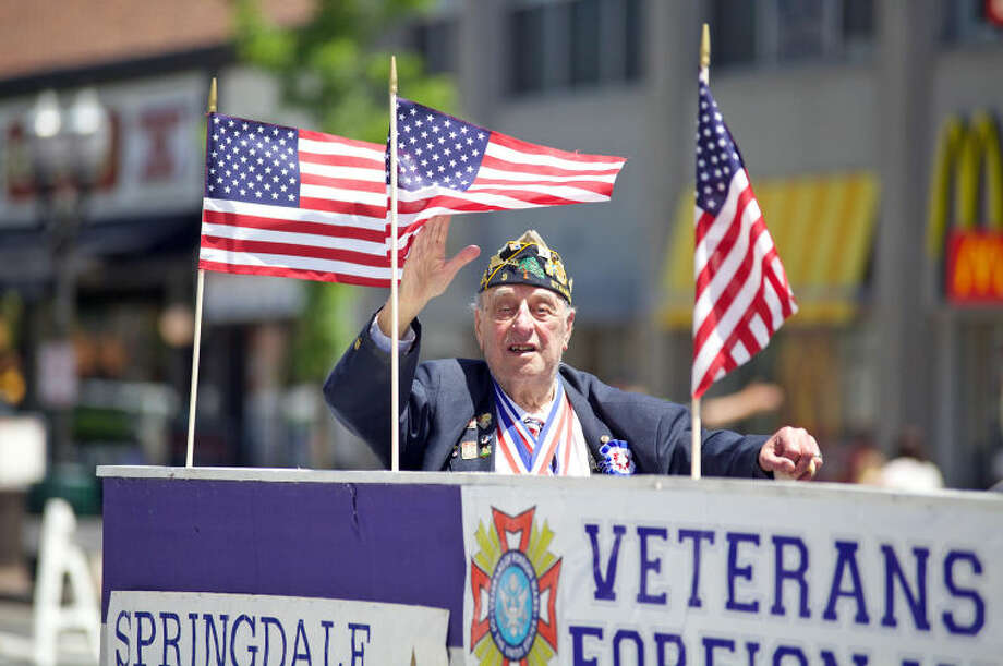 Korean War Veteran Carmine Vaccaro waves to the crows during Stamford's annual Memorial Day Parade Saturday afternoon. Hour Photo / Danielle Calloway