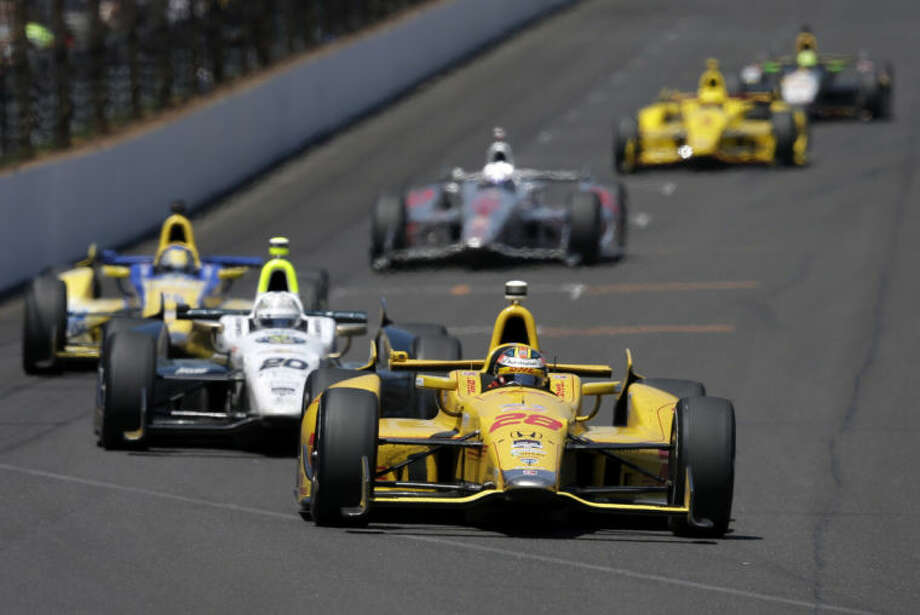 Ryan Hunter-Reay leads Ed Carpenter into the first turn during the 98th running of the Indianapolis 500 IndyCar auto race at the Indianapolis Motor Speedway in Indianapolis, Sunday, May 25, 2014. (AP Photo/Darron Cummings)