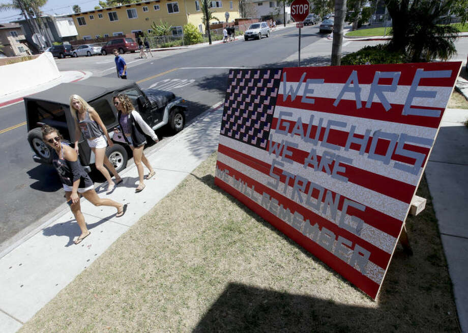 University of California, Santa Barbara students walks past a sign showing support for the college community Sunday, May 25, 2014, in the Isla Vista area near Goleta, Calif. Sheriff's officials said Elliot Rodger, 22, went on a rampage near the UC Santa Barbara campus, stabbing three people to death at his apartment before shooting and killing three more in a crime spree through a nearby neighborhood. (AP Photo/Chris Carlson)