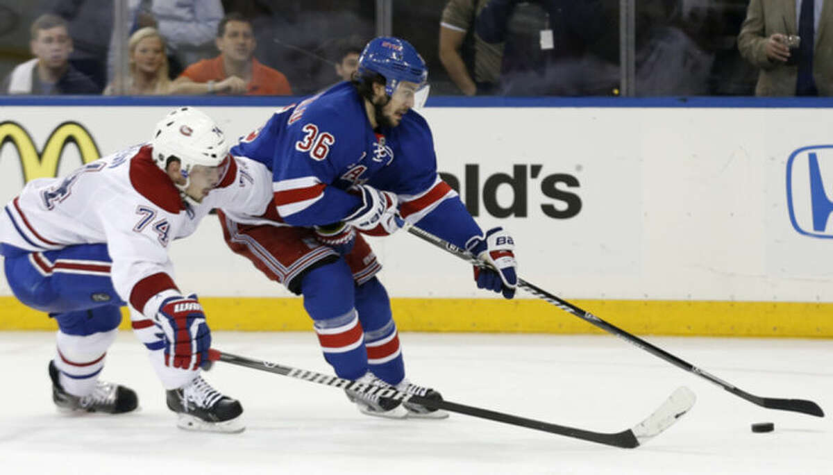 New York Rangers right wing Mats Zuccarello (36) fends off Montreal Canadiens defenseman Alexei Emelin, of Russia, during the second period of Game 4 of the NHL hockey Stanley Cup playoffs Eastern Conference finals, Sunday, May 25, 2014, in New York. (AP Photo/Kathy Willens)
