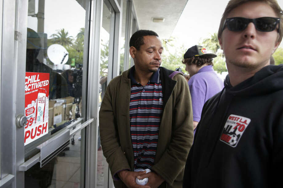 UC Santa Barbara student Derrick Hayes, center, sheds tears in front of IV Deli Mark where Friday night's mass shooting took place by a drive-by shooter on Saturday, May 24, 2014, in Isla Vista, Calif. The shooter went on a rampage near a Santa Barbara university campus that left seven people dead, including the attacker, and others wounded, authorities said Saturday. (AP Photo/Jae C. Hong)