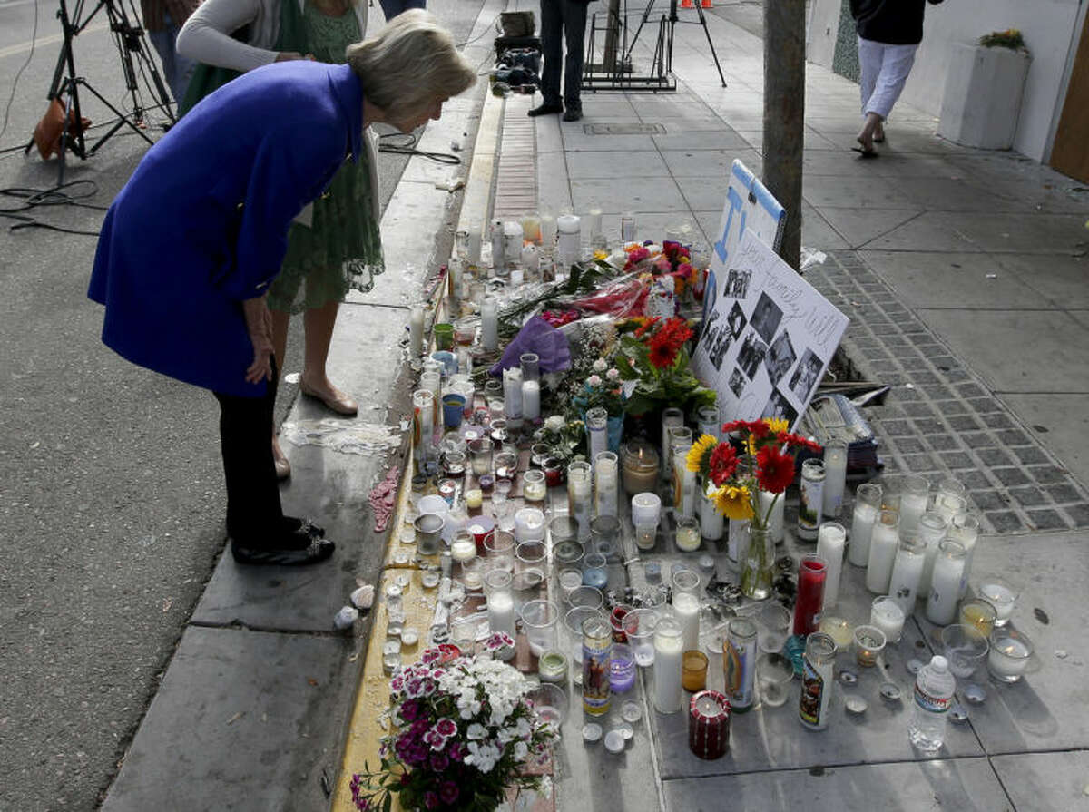 Rep. Lois Capps, D-Santa Barbara, pays her respects at a makeshift memorial in front of the IV Deli Mart, where part of Friday night's mass shooting took place by a drive-by shooter Sunday, May 25, 2014 in the Isla Vista area near Goleta, Calif. Calif. Sheriff's officials said Elliot Rodger, 22, went on a rampage near the University of California, Santa Barbara, stabbing three people to death at his apartment before shooting and killing three more in a crime spree through a nearby neighborhood. (AP Photo/Chris Carlson)