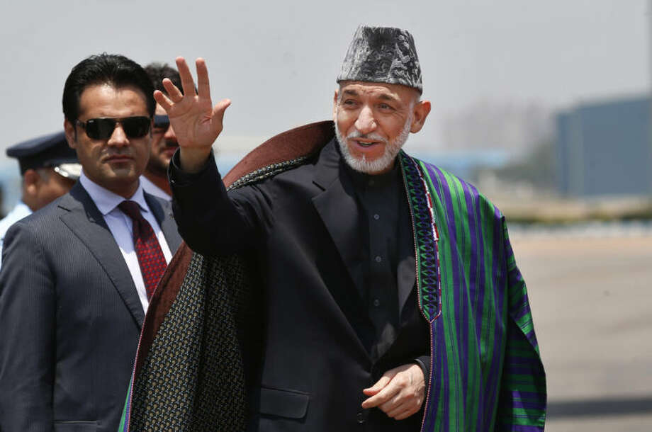 Afghan President Hamid Karzai waves upon arrival for the swearing in ceremony of India's prime minister elect Narendra Modi in New Delhi, India, Monday, May 26, 2014. Security has been tightened across the capital Monday as Modi prepares to be sworn in as prime minister in a ceremony attended by heads of state from across South Asia. (AP Photo/Saurabh Das)