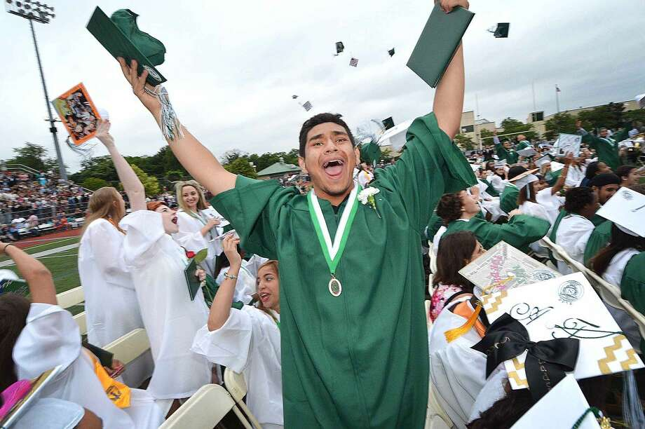 Hour Photo/Alex von Kleydorff Pablo Vanegas celebtrates as graduates throw their caps in the air with the Norwalk High School Class of 2015 at Graduation
