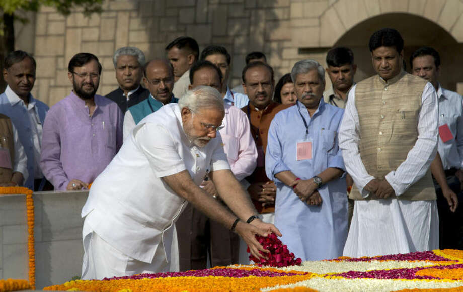 Indian Prime Minister-designate and Hindu nationalist Bharatiya Janata Party leader Narendra Modi pays floral tributes at Rajghat, the memorial of Mahatma Gandhi, in New Delhi, India, Monday, May 26, 2014. Modi, 63, will be sworn-in as the India's Prime Minister on Monday evening by President Pranab Mukherjee at the forecourt of the Indian presidential palace. (AP Photo /Manish Swarup)