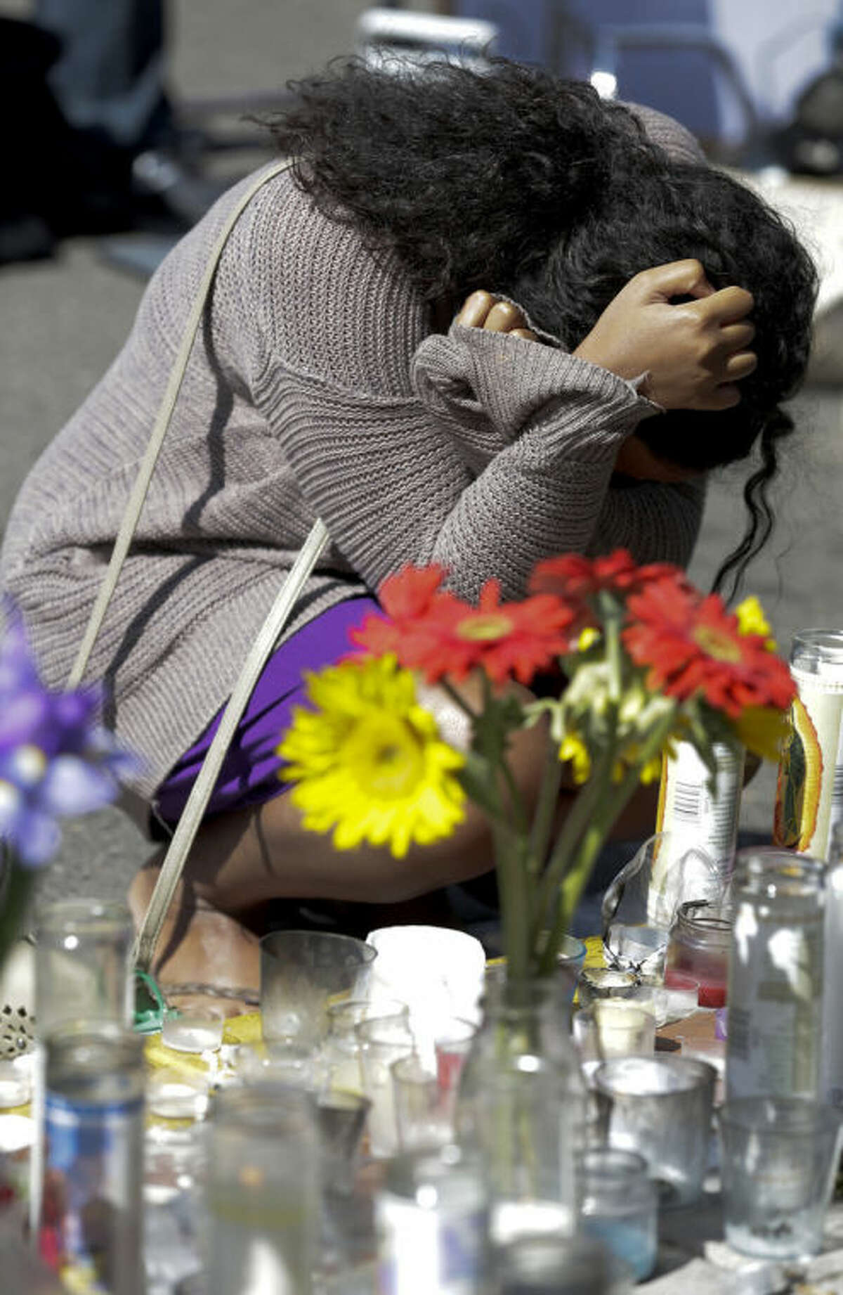 Susana Abdurahman pays her respects at a makeshift memorial in front of the IV Deli Mart, where part of Friday night's mass shooting took place by a drive-by shooter Sunday, May 25, 2014, in the Isla Vista area near Goleta, Calif. Sheriff's officials said Elliot Rodger, 22, went on a rampage near the University of California, Santa Barbara, stabbing three people to death at his apartment before shooting and killing three more in a crime spree through a nearby neighborhood. (AP Photo/Chris Carlson)