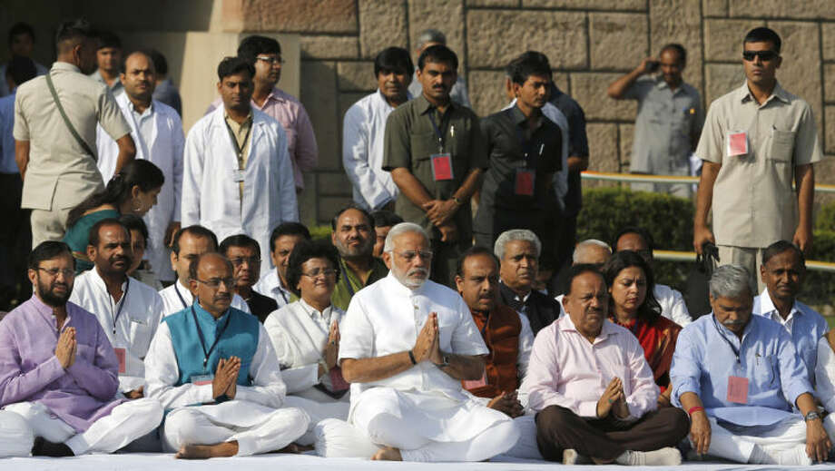Indian Prime Minister-designate and Hindu nationalist Bharatiya Janata Party leader Narendra Modi, center, prays at Rajghat, the memorial of Mahatma Gandhi, in New Delhi, India, Monday, May 26, 2014. Modi, 63, will be sworn-in as the India's Prime Minister on Monday evening by President Pranab Mukherjee at the forecourt of the Indian presidential palace. (AP Photo /Manish Swarup)