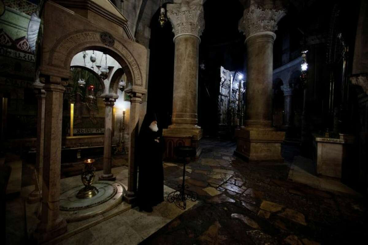 File - In this Friday, May 18, 2012 file photo, Armenian Orthodox priest Father Samuel stands in the Church of the Holy Sepulcher in Jerusalem. Pope Francis and the spiritual leader of the world's Orthodox Christians could not have chosen a more fitting meeting place to promote Christian unity on Sunday than the Jerusalem holy site where their churches' centuries-old rivalries and machinations play out every day. The Church of the Holy Sepulcher, where the pope will meet Ecumenical Patriarch Bartholomew I in the central event of his Holy Land trip, marks the spot where Roman Catholic and Orthodox Christians believe Jesus was crucified, buried and resurrected. (AP Photo/Dusan Vranic, File)