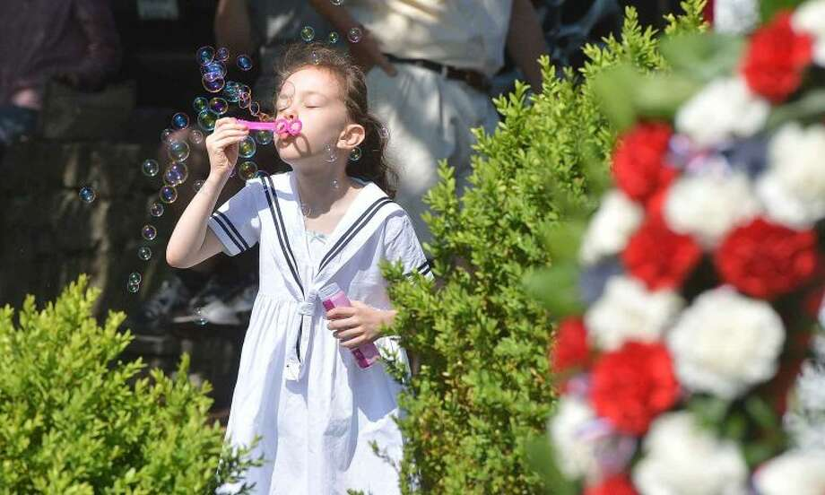 Hour Photo/Alex von Kleydorff 7yr old Lily Tully blows some bubbles as the parade starts in Wilton Center on Monday