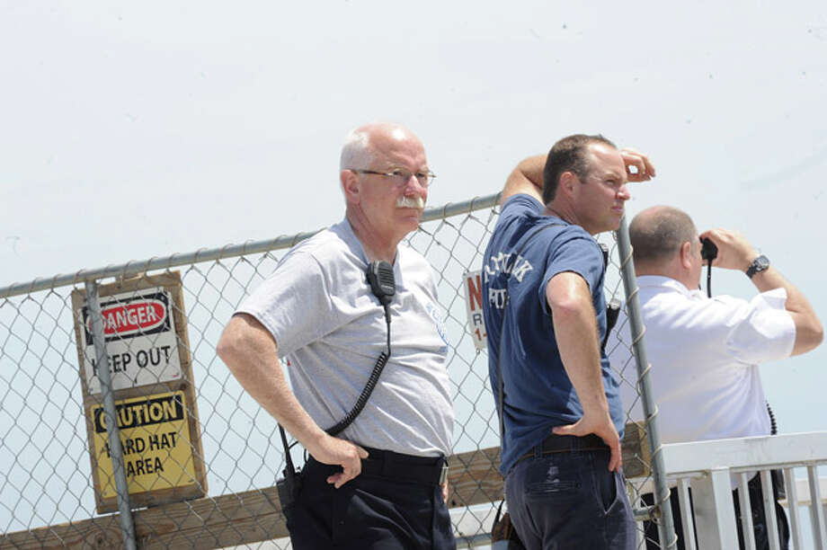 Denis McCarthy Norwalk Fire Chief waits on the pier at Calf Pasture Beach Monday where a member of boat that turned over in the water went missing. Hour photo/Matthew Vinci