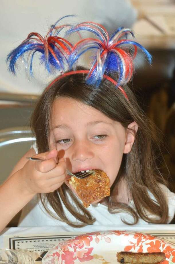 Hour Photo/Alex von Kleydorff Arden Taubin trys to get a whole pancake in her mouth at the Wilton Kiwanis Pancake Breakfast at The Wilton Congrgational Church before the parade