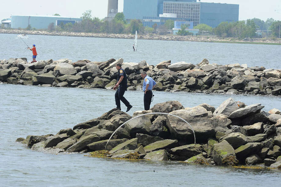 Norwalk police search the shoreline at Calf Pasture Beach Monday where one of four boaters went missing after the boat turned over. Hour photo/Matthew Vinci