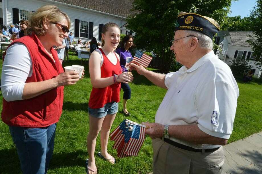 Hour Photo/Alex von Kleydorff Ken Dartley passes out flags donated by American Legion Post 86 in Wilton