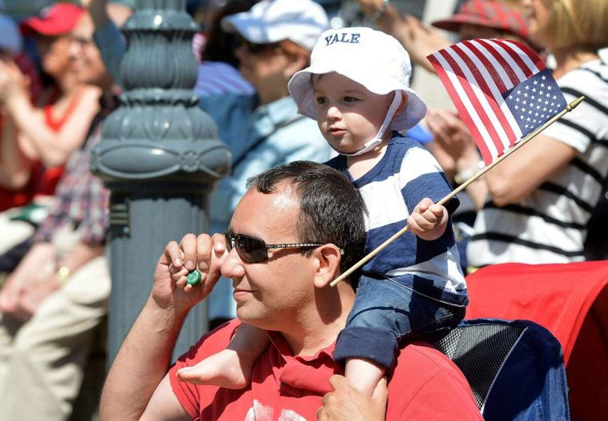Hour Photo/Alex von Kleydorff 16 Month old Jagger Batista waves the flag on his dad Davids shoulders as Wilton's Memorial Day Parade makes its way through the town center on Monday