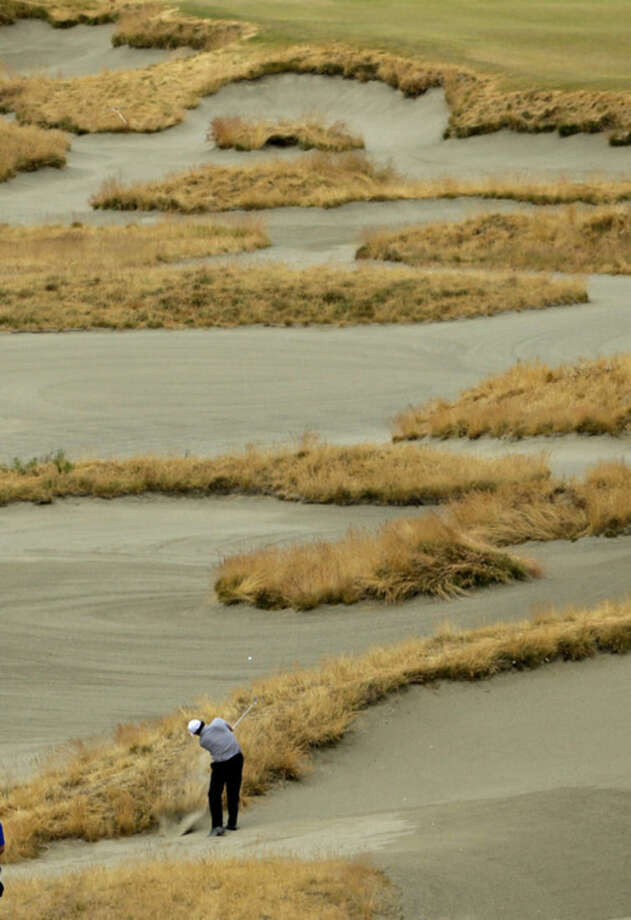 Phil Mickelson hits out of a fairway bunker on the 14th hole during the first round of the U.S. Open golf tournament at Chambers Bay on Thursday, June 18, 2015 in University Place, Wash. (AP Photo/Ted S. Warren)