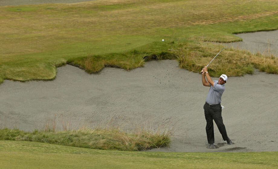 Phil Mickelson hits out of the bunker on the 13th hole during the first round of the U.S. Open golf tournament at Chambers Bay on Thursday, June 18, 2015 in University Place, Wash. (AP Photo/Ted S. Warren)