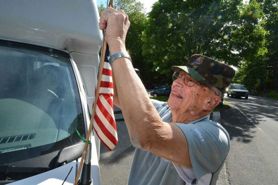 Hour Photo/Alex von Kleydorff Ross Hand places a flag on the Wilton senior services bus he drives during Memorial Day in Wilton