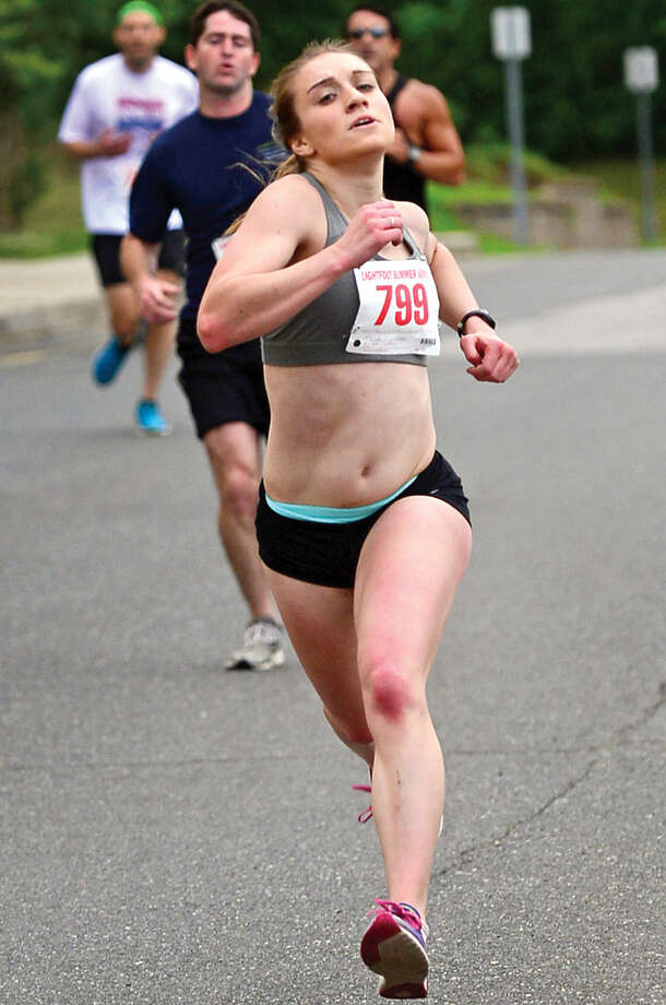 Hour photo / Erik Trautmann Lindsey Russo is the first female finsher during the summer's first Lightfoot running series race, a 3-miler, at Norwalk High School Saturday.