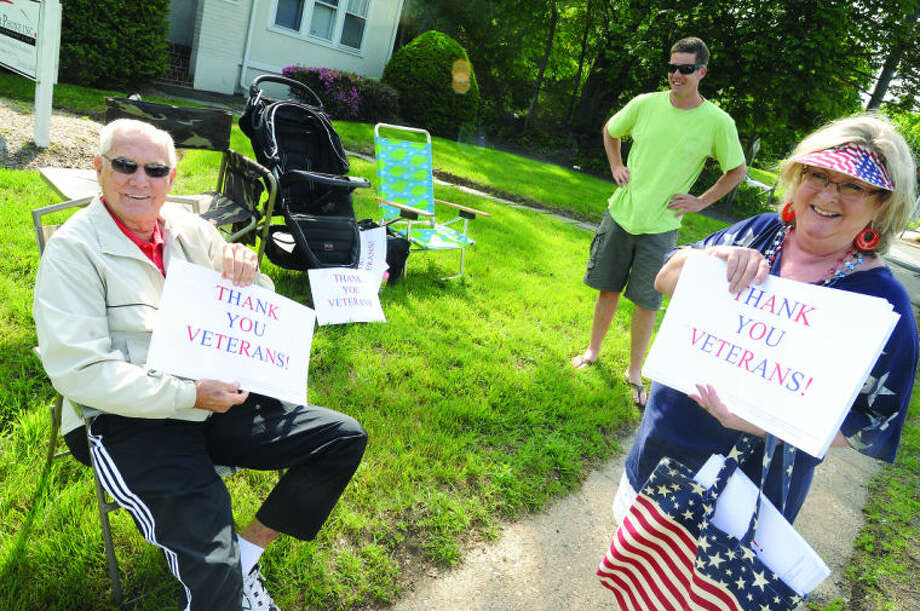 Chic Jacoby Korean War Navy veteran gets his sign from volunteer Diane Cece at the Memorial Day Parade in Norwalk on Monday. Hour photo/Matthew Vinci