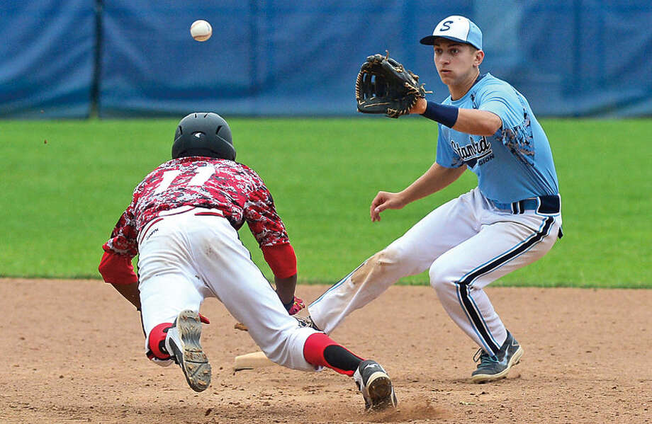 Hour photo / Erik Trautmann Stamford American Legion baseball 2nd baseman Johnny Spodo tries to get the tag on Norwalk's Edwin Owolo during their double-header at Cubeta Stadium Saturday.