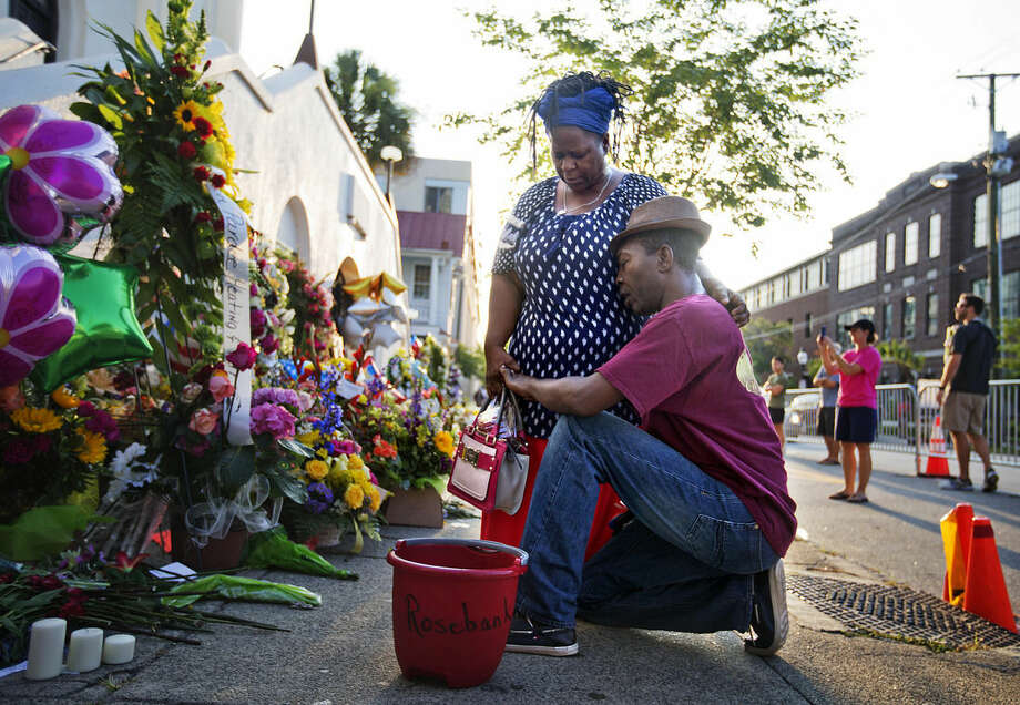"Allen Sanders, right, kneels next to his wife Georgette, both of McClellanville, S.C., as they pray at a sidewalk memorial in memory of the shooting victims in front of Emanuel AME Church Saturday, June 20, 2015, in Charleston, S.C. ""You can't have love and hate residing in the heart at the same time,"" said Georgette. ""We're just going to have to love one another,"" her husband added. (AP Photo/David Goldman)"