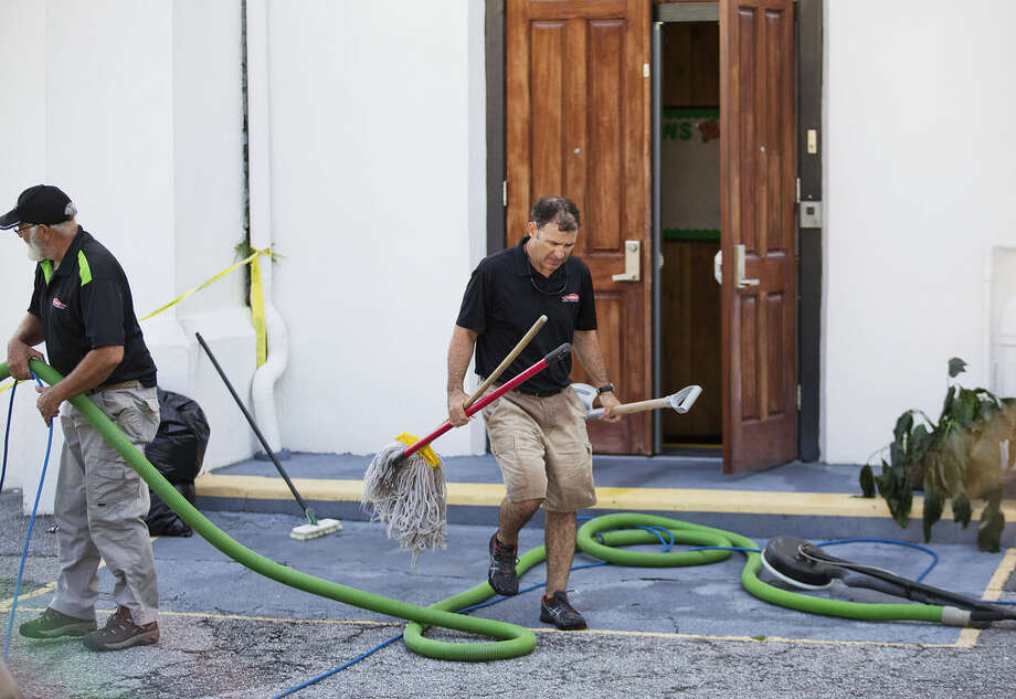 A cleaning crew moves equipment while working at the Emanuel AME Church where nine people at the historic black church were killed Wednesday in a shooting in Charleston, S.C., Saturday, June 20, 2015. (AP Photo/David Goldman)