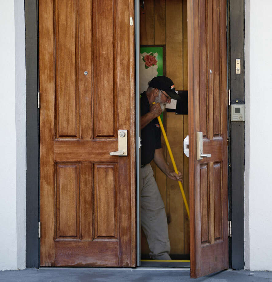 A member of a cleaning crew mops a floor inside the Emanuel AME Church where nine people at the historic black church were killed Wednesday in a shooting in Charleston, S.C., Saturday, June 20, 2015. (AP Photo/David Goldman)