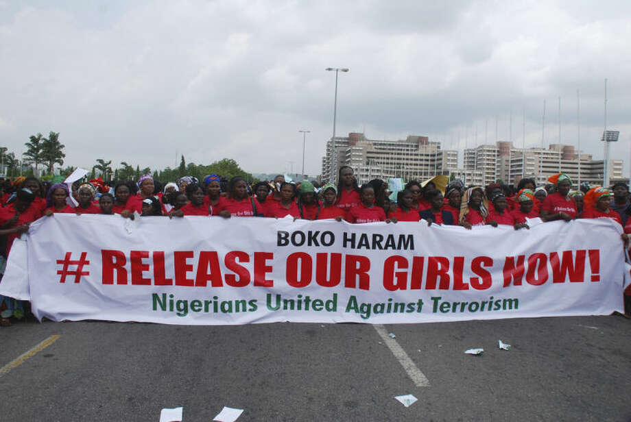 """The Nigerians United Against Terrorism group attend a demonstration calling on the government to rescue the kidnapped girls of the government secondary school in Chibok, in Abuja, Nigeria, Monday, May 26, 2014. Scores of protesters chanting """"Release our girls now"""" marched in the Nigerian capital Monday to protest the abductions of more than 300 schoolgirls by Boko Haram, the government's failure to rescue them and the killings of scores of teachers by Islamic extremists in recent years. (AP Photo/Gbenga Olamikan)"""