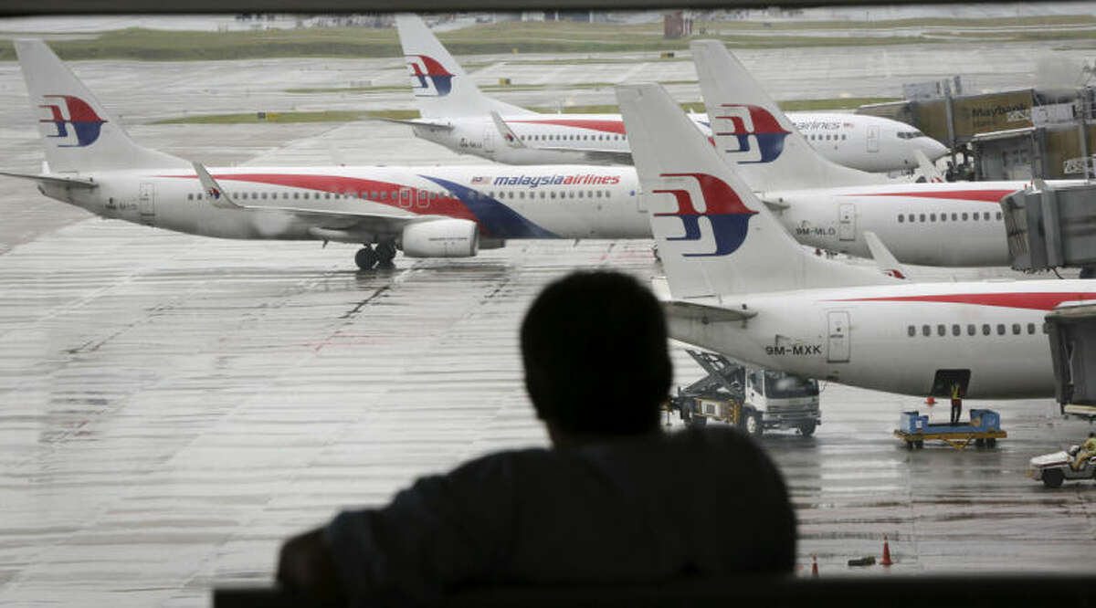 A visitor looks out from the viewing gallery as Malaysia Airlines aircraft sit on the tarmac at the Kuala Lumpur International Airport (KLIA) in Sepang, Malaysia, Tuesday, May 27, 2014.