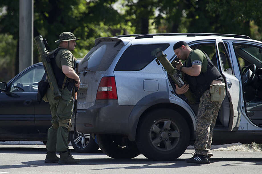Pro-Russian insurgents arrive with weapons, near the airport outside Donetsk, Ukraine, Monday, May 26, 2014. Ukraine's military launched airstrikes Monday against the separatists who had taken over the airport in the eastern city of Donetsk, suggesting that fighting in the east is far from over. (AP Photo/Ivan Sekretarev)