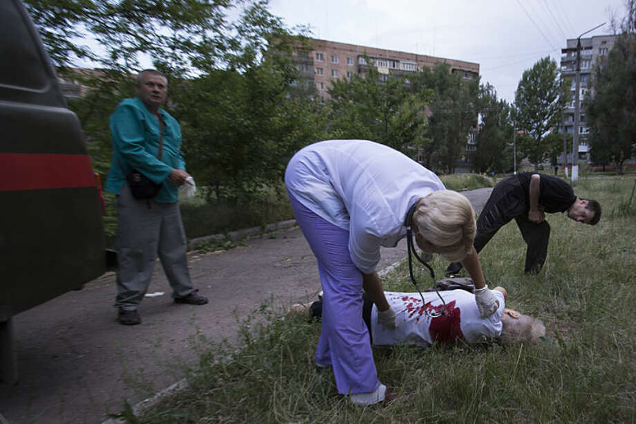 "Local ambulance medics run to the body of Olga Prokhorenko, 60, killed by shrapnel following a shelling from Ukrainian government forces in Slovyansk, Ukraine, Monday, May 26, 2014. Exit polls from Sunday's first round of the new presidential election predict Petro Poroshenko will be elected president in this bitterly divided country, and he vowed ""to bring peace to the Ukrainian land"", yet he described the separatists as ""Somali pirates"" and authorities in Kiev launched strikes against the militants.(AP Photo/Alexander Zemlianichenko)"