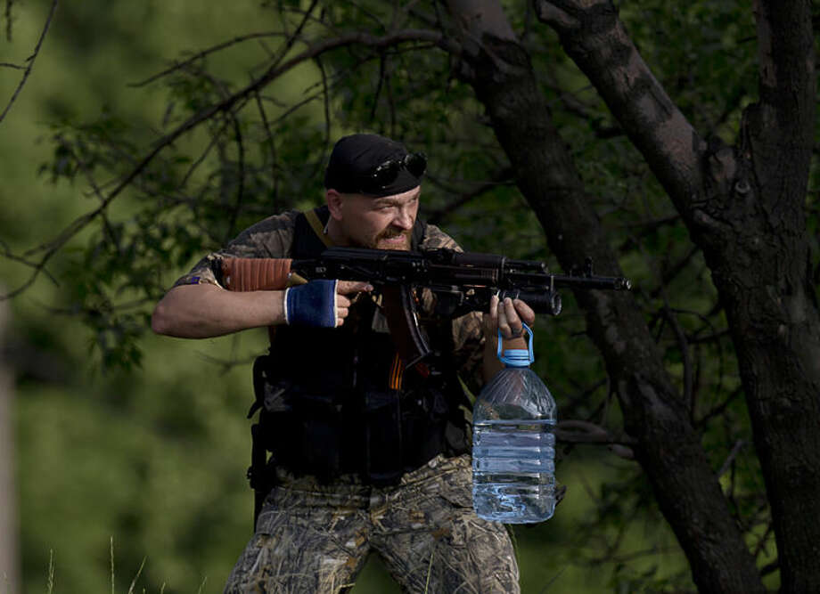 A pro-Russian gunman aims his weapon near the airport, outside Donetsk, Ukraine, on Monday, May 26, 2014. Ukraine's military launched air strikes Monday against separatists who had taken over the airport in the eastern capital of Donetsk in what appeared to be the most visible operation of the Ukrainian troops since they started a crackdown on insurgents last month. (AP Photo/Vadim Ghirda)