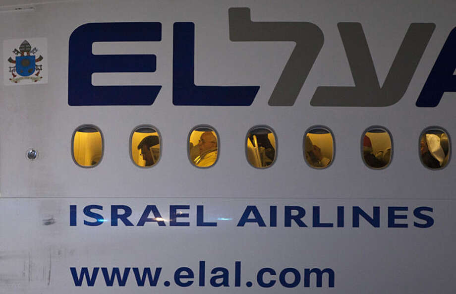 Pope Francis is seen though a window, 3rd from left, aboard an El Al aircraft as the Pontiff leaves Israel following an official departure ceremony at Ben Gurion airport near Tel Aviv, Israel, Monday, May 26, 2014. (AP Photo/Dan Balilty)