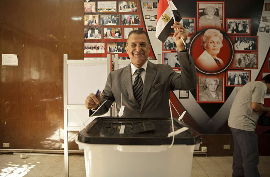 An Egyptian casts his ballot for President in an election that comes nearly a year after the military's ouster of the nation's first freely elected president, the Islamist Mohammed Morsi, in Cairo, Egypt, Monday, May 26, 2014. The man who removed Morsi, retired military chief Field Marshal Abdel-Fattah el-Sissi, is practically assured of a victory in the vote. (AP Photo/Maya Alleruzzo)