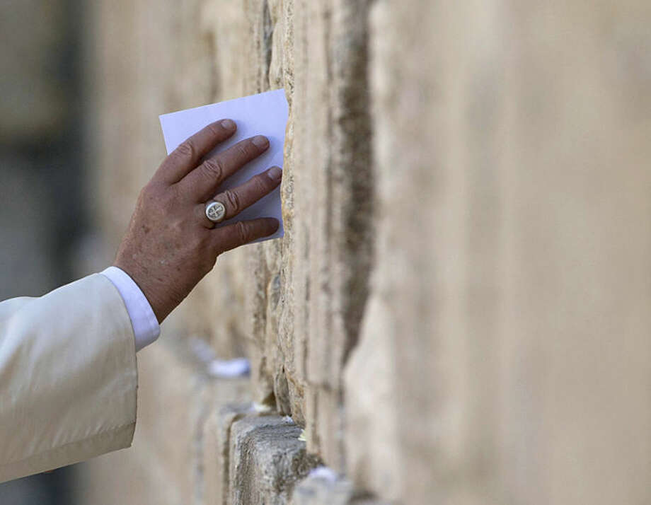 RETRANSMITTING TO PROVIDE TIGHT CROP OF AJM101. Pope Francis places an envelope in on of the cracks between the stones of the Western Wall, the holiest place where Jews can pray, in the old city of Jerusalem, Israel, Monday, May 26, 2014. (AP Photo/Andrew Medichini)
